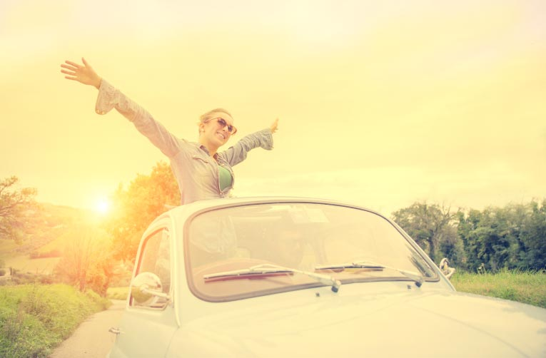 Happy woman riding out of sunroof in sunshine